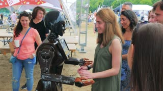 Moscow, Russia - Jun 15, 2016: The robot with interactive display communicates with visitors in public place. People using his touch screen. High tech system today. Innovative assistant in society