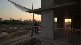 Moscow.Russia 05.2016.Construction work at sunset, industry and development. The camera moves around the Builder in the rays of the setting sun