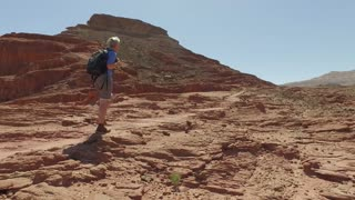 Mountain tourism and recreation. Walking in the desert.Girl with a backpack walking along the stone red desert. Steady shot