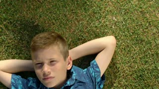 Portrait of a teenage boy lying in the grass. Child relaxing in a field in spring, summer.