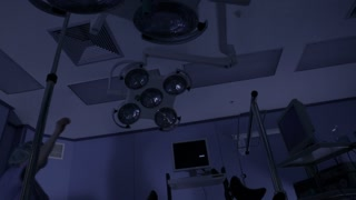 Preparation for surgery. Disinfection and the inclusion of light in the operating room. Nurse turns on the lamp in the operating room