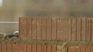 Professional Builder lays bricks at a construction site. Dolly shot, closeup