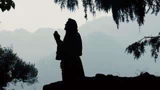 Silhouette of a praying man in a hoodie on nature background