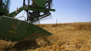 The agro-industry . Harvester gathers the grain harvest . The plow in the foreground