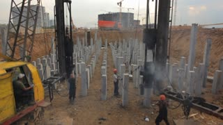 The building of docks and factories . Diesel hammer scored piles. The camera moves around the site