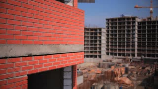 The construction of the condominium . The camera goes up along the wall of a brick house. In the background an unfinished house