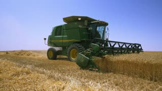 The development of agriculture . Combine harvest grain from the fields