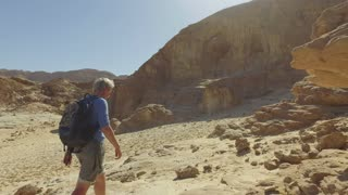 Tourist explores the stone desert in the middle East.Steadycam shot of climber