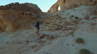 Tourist routes in the desert and mountains. Aerial.Climber in equipping exploring new places.Steady shot