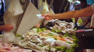 VENICE, ITALY - JUNE 20, 2016: Buying of fresh seafood and fish at a market Rialto, Venice, Italy