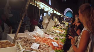 VENICE, ITALY - JUNE 20, 2016: Shoppers choose fresh seafood and fish at a market Rialto, Venice, Italy