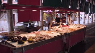 VENICE, ITALY - JUNE 20, 2016: Tourists choose fresh seafood and fish at a market Rialto, Venice, Italy