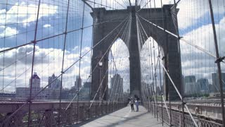 Architecture of New York. Tourists are walking along the Brooklyn Bridge. Steadycam shot