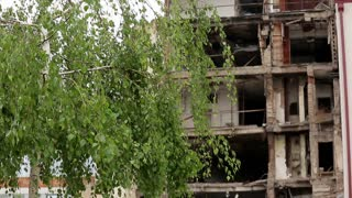 Belgrade. The consequences of NATO bombing in 1999. Destroyed building on green tree background.
