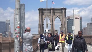 Brooklyn Bridge at the height of the working day. Tourists and New Yorkers go to work. Dolly shot