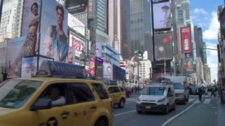 Car traffic in Manhattan. Panoramic shot of cars and skyscrapers with billboards. Times Square.