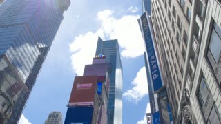 Center of the universe - Times Square. Skyscrapers with electronic billboards. The camera moves between the buildings.