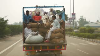 Delhi, India - Sept 29, 2016: Unidentified travellers on a truck at Delhi. Transport for workers is often overcrowded.