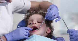 Dental examination of the oral cavity of the child . Patient in modern dental сabinet. Doctors make an inspection. Shot on red , dolly shot