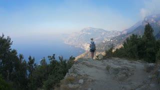 Italy. The Amalfi coast. A tourist on the edge of the cliff.
