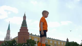 Moscow. Manezhnaya square. Young football player takes the ball on his chest.
