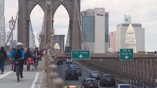 Pedestrian and car traffic on the Brooklyn Bridge in New York City. Dolly shot .