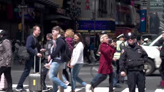 Pedestrian and car traffic on the streets of Manhattan. Police, tourists, workers. Dolly shot.