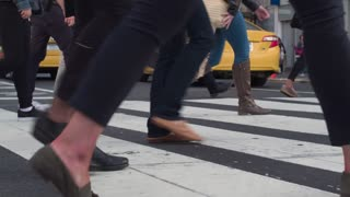 Pedestrian traffic at the crossroads in the center of Manhattan. People cross the road. Steadycam shot