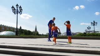 RUSSIA, MOSCOW - 24 may 2018: Football coach and two young athletes playing football on Manezh square in Moscow.