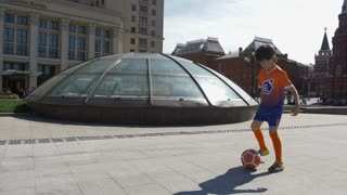 RUSSIA, MOSCOW - 24 may 2018: The young football player shows the excellent technique of possession of the ball against the background of the historical Museum of Moscow.