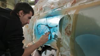 RUSSIA, MOSCOW - 8 JUN 2017: Airbrushing on the car. The master puts a picture with butterflies.