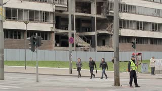 SERBIA, BELGRAD - 11 may 2017: Passers-by on the street of modern Belgrade on the background of the building, destroyed by the bombing of NATO forces.