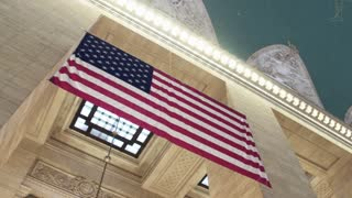 Symbols of the state of the United States of America. The US flag on the Grand Central. Dolly shot.