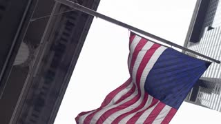 The American flag flutters in the wind on the backdrop of the skyscrapers of the financial quarter in New York City. Close-up..
