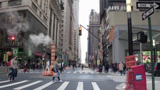 The atmosphere of the city of New York and Manhattan. Pedestrian crossings, smoking chimneys, skyscrapers, shops. Dolly shot.