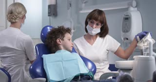 The child is not afraid of the dentist. Patient in modern dental сabinet. Doctors make an inspection. Shot on red , dolly shot