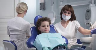 The kid in the dentist chair. Positive emotions. Patient in modern dental сabinet. Doctors make an inspection. Shot on red , dolly shot