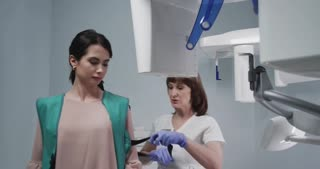 The technician puts the patient in a protective vest before the procedure x-rays. Patient in modern dental сabinet. Doctors make an inspection. Shot on red , dolly shot