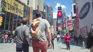 Tourist walks in New York. Tourists take photos of the attractions of Times Square. Steadicam shot.