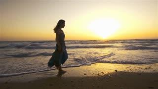 Woman walking on beach barefoot over sunset.