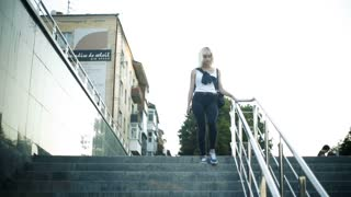 A young blond woman walks down the stairs in the city. Moves towards the camera.