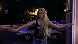 A young blond woman with very long flowing hair dances near the hotel's window lit by yellow lights. Night, outdoor Slowmotion Balet