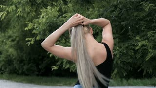 A young blonde woman with very long hair collects them in the tail. It is located in the park in Gord. Outside. Outdoor Slowmotion