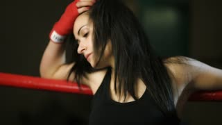 A young girl, a Latino woman, hung on the ropes of the ring, straightening her black hair. She looks thoughtfully.