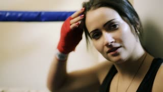 A young girl, a Latino woman sits in the corner of the ring, straightens her hair, looks into the camera