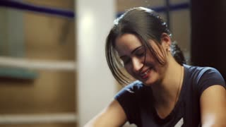 A young latino woman girl genuinely laughs, sitting in the ring, near the boxing pear. There can not be laughter