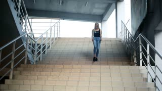 A young sexy blond woman with very long flowing hair goes down the stairs, looks into the camera.
