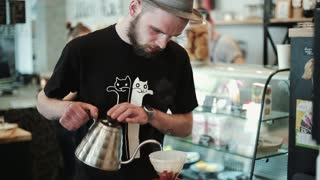 Barista pours hot water into the filter with coffee, stirring. Prepares Pour Over, Chemex Barista with a beard. Pump