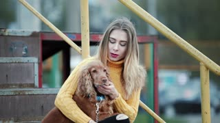 Blonde girl woman and dog cocker spaniel. she strokes the dog, cares, kisses, smiles in the evening in the city. On the background of metal rusty steps. who looks like Jennifer Aniston