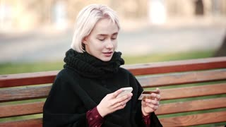 Blonde woman girl outside. In the hands of a smartphone and a gold credit card. Sits on a wooden bench. Writes this gold debit card to the smartphone. Performs payment transactions.